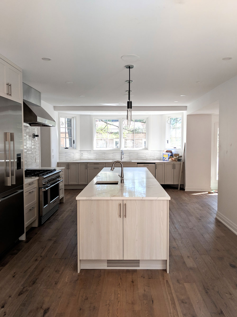 Photo of a modern light-coloured kitchen with a wooden floor with a beautiful center isle