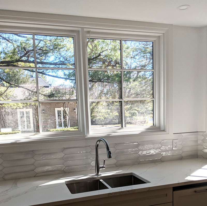 Photo of a modern kitchen sink in front of beautiful classic windows